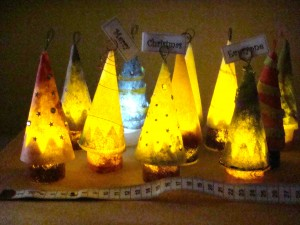 Eleven Lutradur Christmas trees illuminated by battery operated tea lights.
