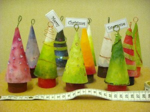 Eleven little Christmas trees decorated in shades of green and red and decorated with tiny coloured beads and wire.