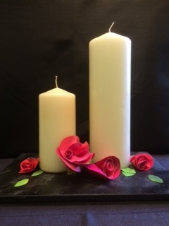 Two large cream candles with red Evolon roses and green Evolon leaves standing on a dark slate tile.