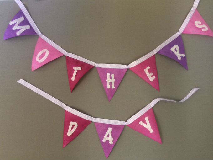 Pretty shades of pink, mauve and purple bunting attached to white ribbon. Each flag has a white letter attached, which linked together spells Mothers Day.