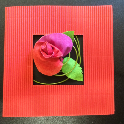 A red Evolon rose peeping out of a square cut hole in the middle of a red Valentine's card.