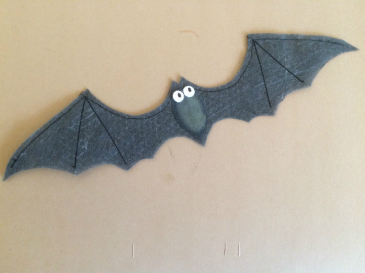 Lutradur Black fabric bat with outstretched wings defined by black machine stitching, grey body and wide white eyes with black pupils.