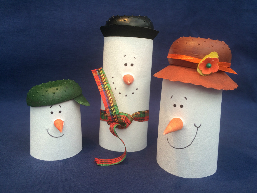 Three cylindrical little snowmen all made from Evolon, with drawn on faces, orange pointy noses and coloured hats.