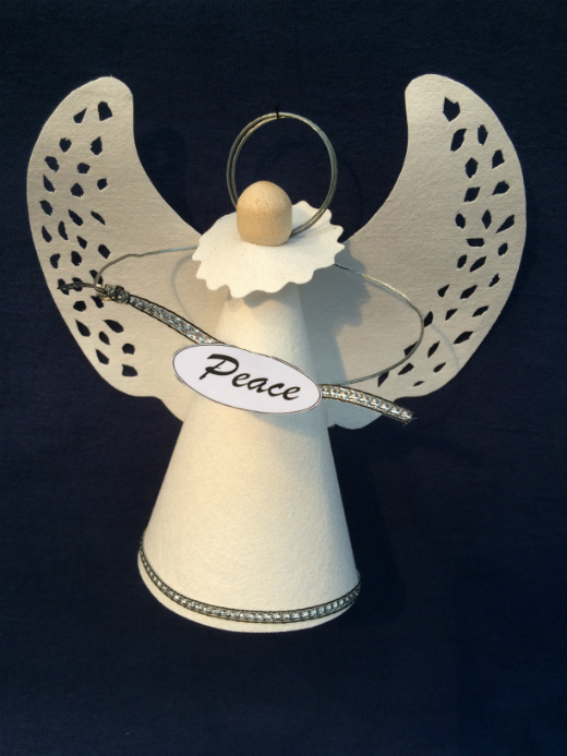 A wooden clothes peg, dressed in a white conical Evolon dress and wings, with circular wire halo and arms holding a sign saying 'Peace'. The wings have tiny holes on the outer edges forming a random pattern.