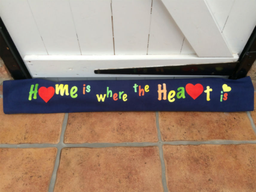 A dark blue draught excluder, made out of Evolon, resting on a brown tiled floor, against a white painted door. The draught excluder is decorated with the words 'Home is where the Heart is' in red, green and yellow lettering. The 'o' in Home and the 'r' in Heart are represented by large red hearts.