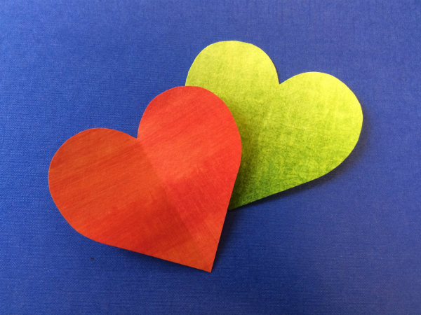 Two hearts made of Evolon. One red and one lime green on a dark blue background. The red heart is resting on top and overlaps the lime green heart.