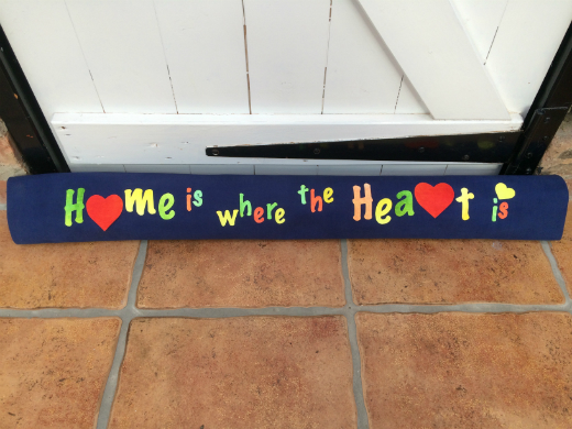 Dark blue draught excluder embellised with transfer painted Evolon lettering 'Home is where the Heart is' in shades of green, yellow and orange. A red heart shape replaces the 'o' in Home and the 'r' in Heart.