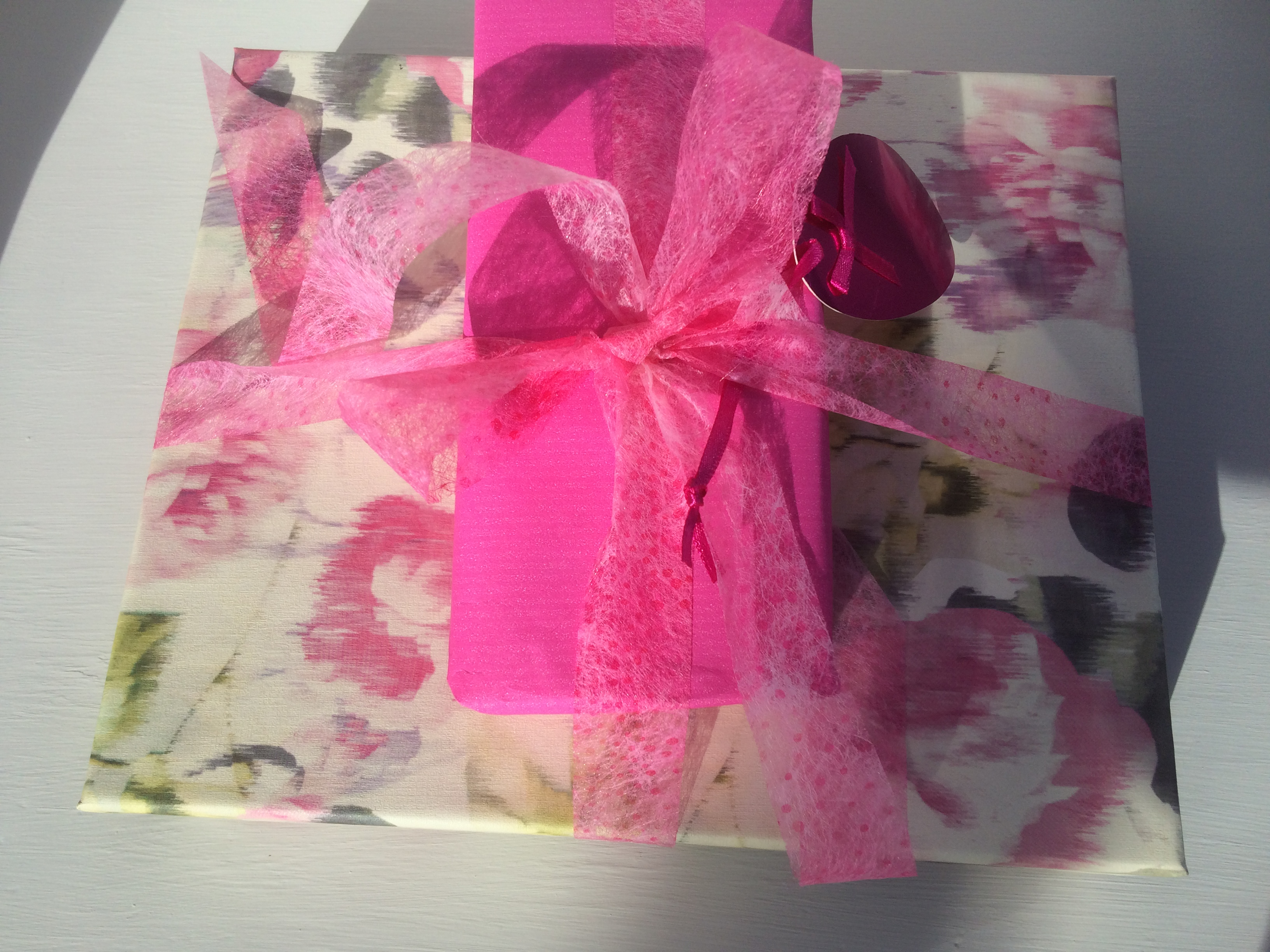 Gift wrapped in pink and white floral paper decorated with a Lutradur bow which has been coloured a vivid pink.