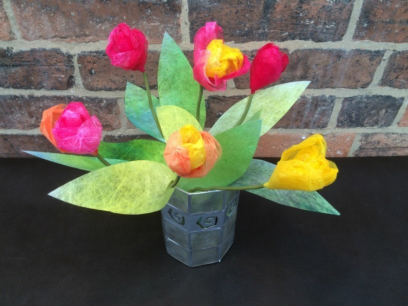A vase of tulips made using Lutradur 25 colours are red, yellow and pink