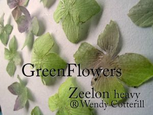 Approximately ten green flowers set on a white canvas and placed in a symmetrical pattern to form a piece of wall art.