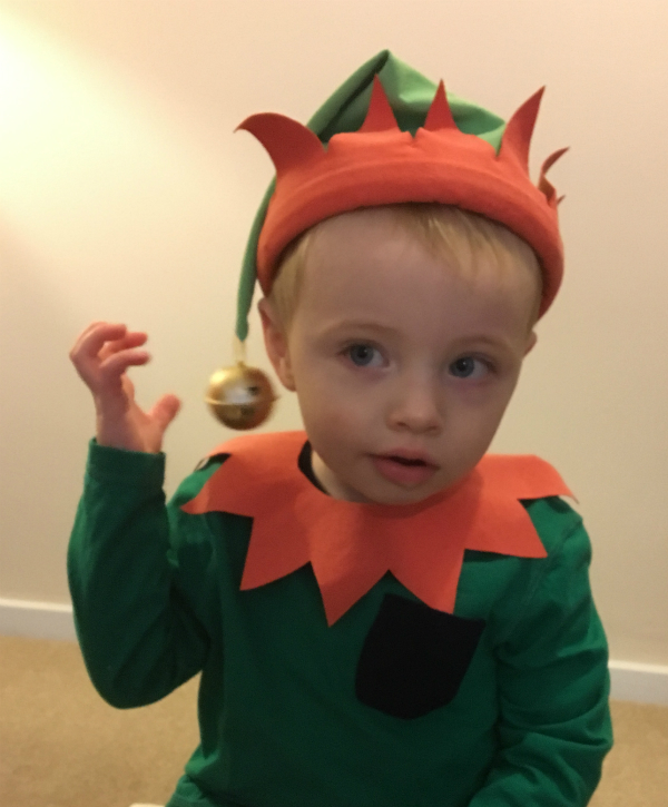 Same little boy, playing with the bell on his elf's hat.
