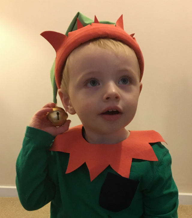 Little boy wearing a dark green t-shirt, light green elf's hat with a red brim and matching pointy collar.