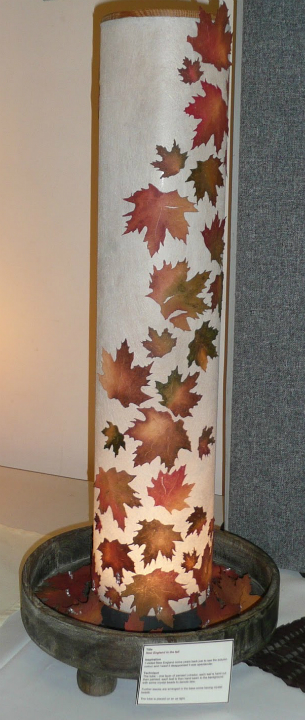 Tall cylindrical lamp made out of Lutradur 100, decorated with leaves of various sizes and shades of autumn colours.