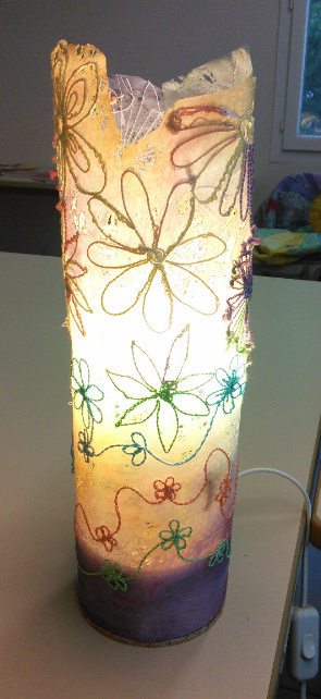 Photograph of the same lamp lit up, showing the detail at the top where the Lutradur has been cut away and burnt.