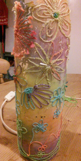 Cylindrical table lamp embroidered with flower outlines in varigated thread on a multi coloured background.