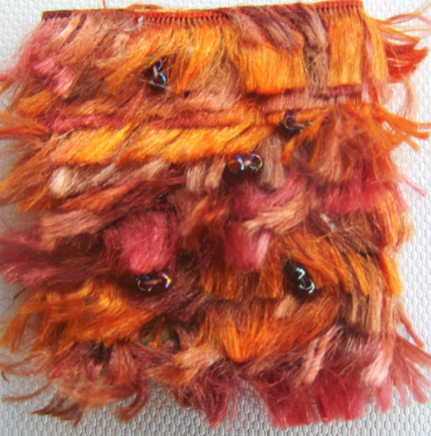 A square brooch decorated with strands of fringed thread in various shades of orange and pink wrapped horizontally and embellished with a few tiny black beads.