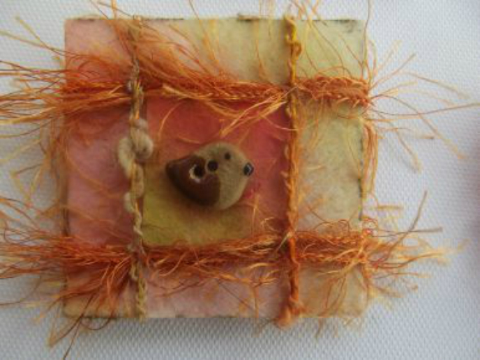 A square brooch with pale green and orange painted background, decorated with four straight strands of wispy thread around a central bird shaped button.