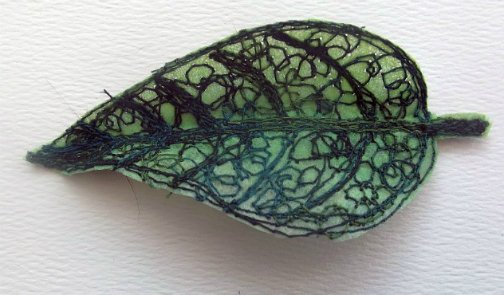 A birch leaf made out of Lutradur which has been dyed pale green and then embellished with machine stitching to create the veins in the leaf.