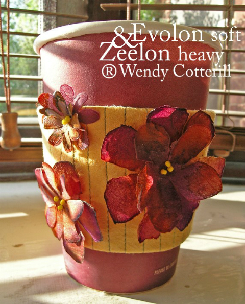 A red paper coffee cup, decorated with a yellow band of Evolon Soft with parallet lines of machine stitching running from top to bottom and decorated with reddish flowers made out of Zeelon Heavy with tiny yellow beads in their centres.