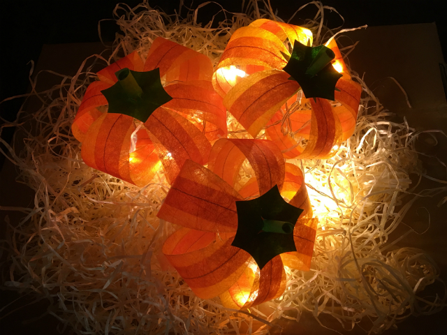 Three orange pumpkins made out of Lutradur and Evolon, resting on straw and illuminated by battery operatd fairy lights.