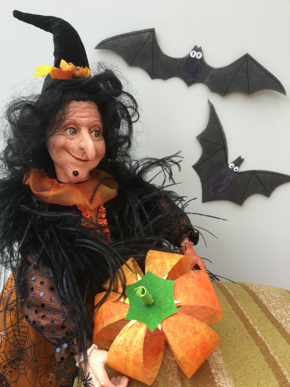 Smiling witch, dressed in orange and black with crooked witch's hat, holds a orange pumpkin made out of Lutradur, with two bats behind her, made out of Lutradur Black.
