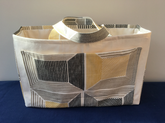 A large cream bag with geometric design on the front and matching wide fabric handles