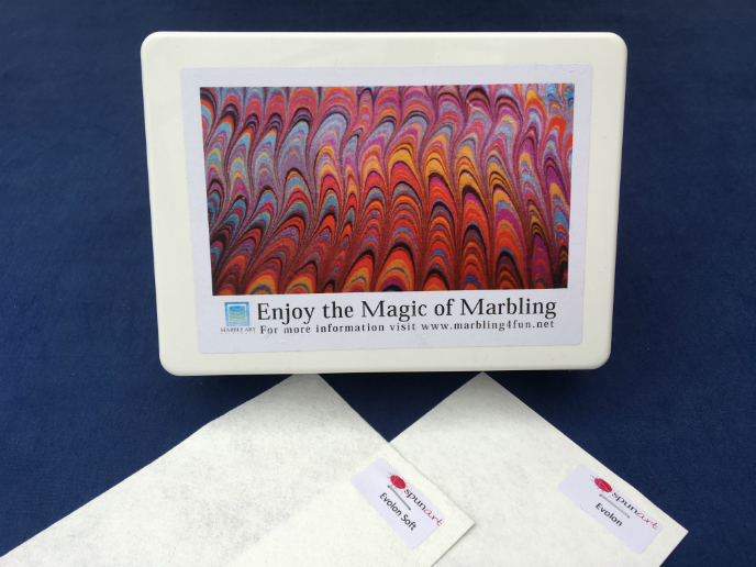 'Enjoy the Magic of Marbling' printed on patterned lid of small white box and samples of Evolon and Evolon Soft.