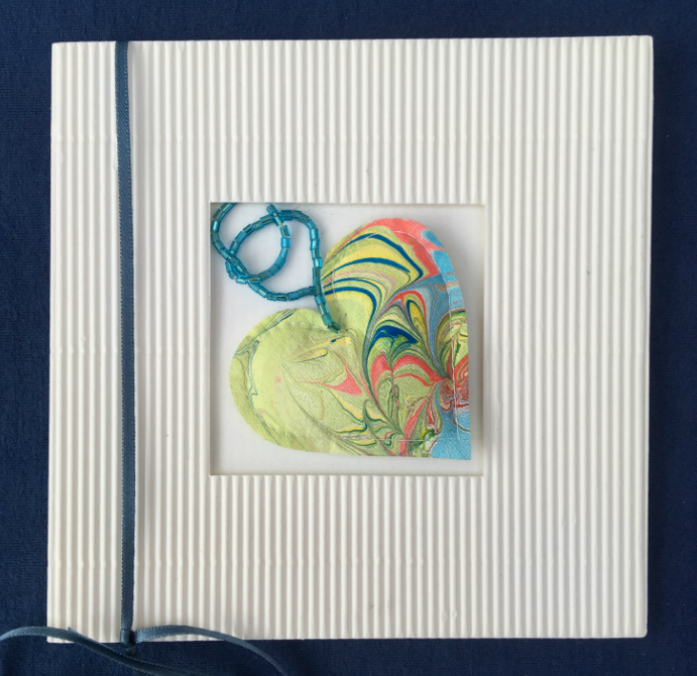 Square white corrugated greetings card with central square aperture containing a small 'marbled' delicately decorated stuffed heart attached to a thread of small blue bugle beads.