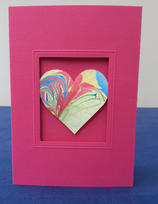 Deep pink card with cut out centre panel, inset with small multi-coloured Evolon heart.