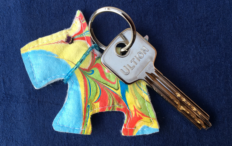 Scottie type dog key fob made of marbled Evolon Soft, decorated with a collar of blue beads.