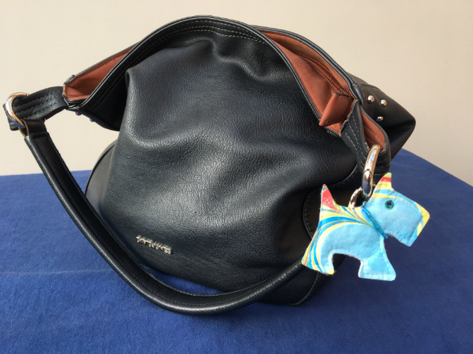 Navy handbag with Scottie dog charm made of marbled Evolon, decorated with a collar of pale blue beads.