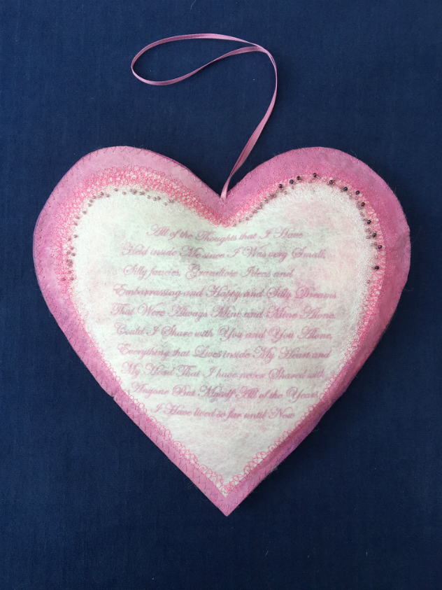Pink heart with white heart shaped printed centre panel, with pink hanging ribbon and decorated with machine embroidery and tiny beads
