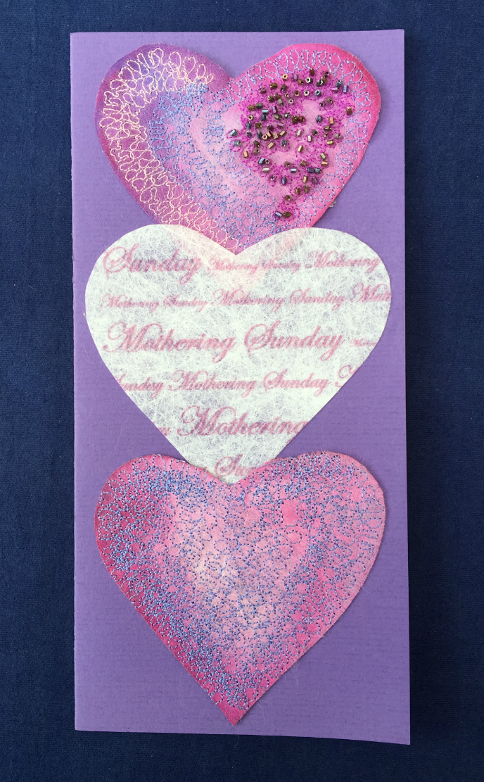 Tall purple card decorated with three hearts, decorated with printed text, free machine stitching and tiny beads.