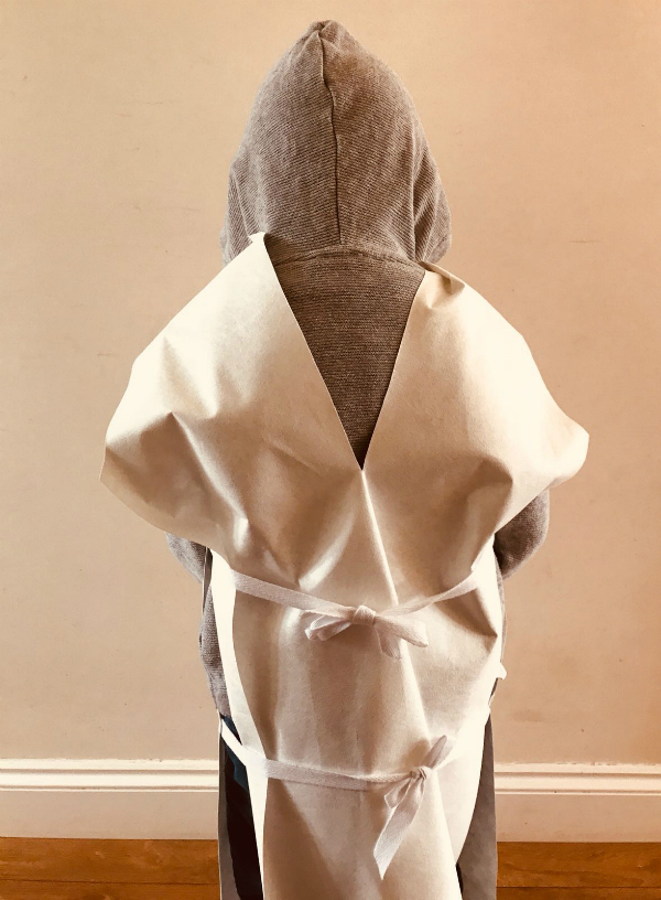 Back view of little boy wearing grey hoodie and white tunic top, showing tie fastenings.