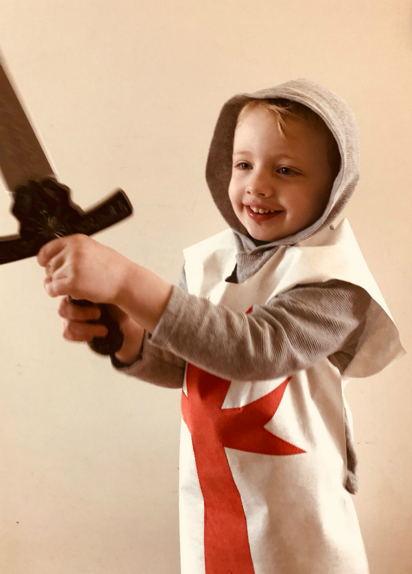 Small boy weilding a toy sword, wearing a grey hoodie under white Evolon tunic with large red cross on the front