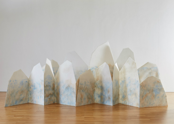 Three mountain ranges made of Lutradur and dappled with diluted blue, brown and white acrylic paint.