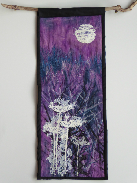Purple and blue background with white, grey, blue and black undergrowth in the foreground, lit by a full moon sparsely covered with light cloud.