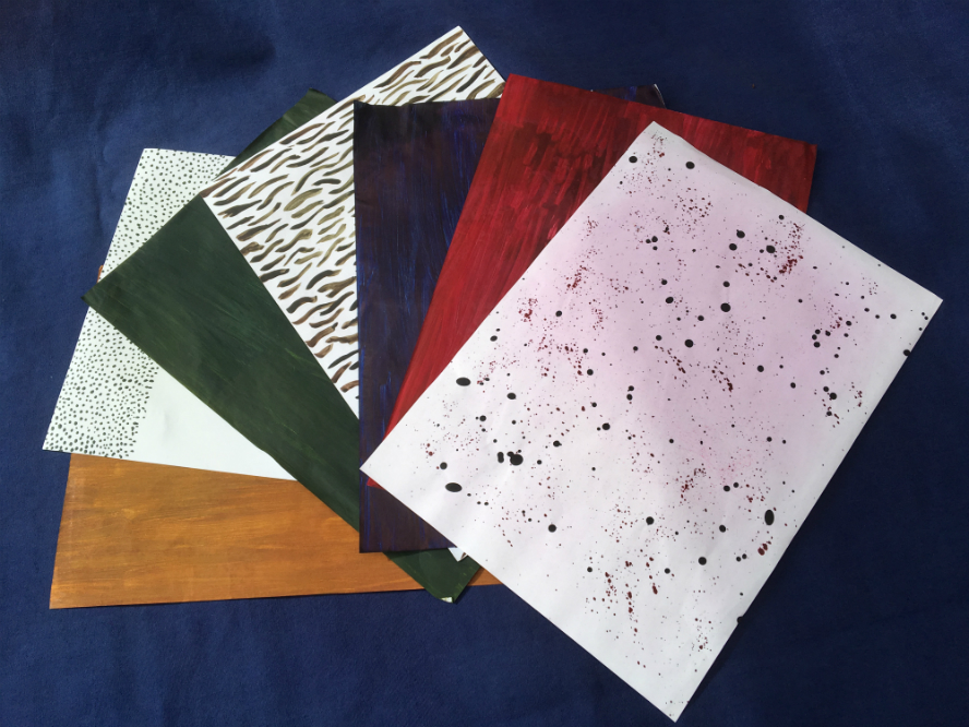Sheets of A4 paper painted with transfer paints in yellow, green, blue and red and also with various designs, such as dots, dashes and wiggly lines.