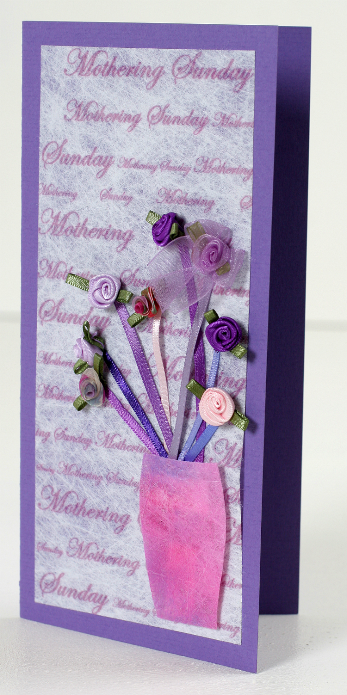 A lilac coloured card with white inset repeating the words Mothering Sunday, embellised with a pink vase containing 8 stems made of thin ribbon with contrasting curled ribbon flowers.