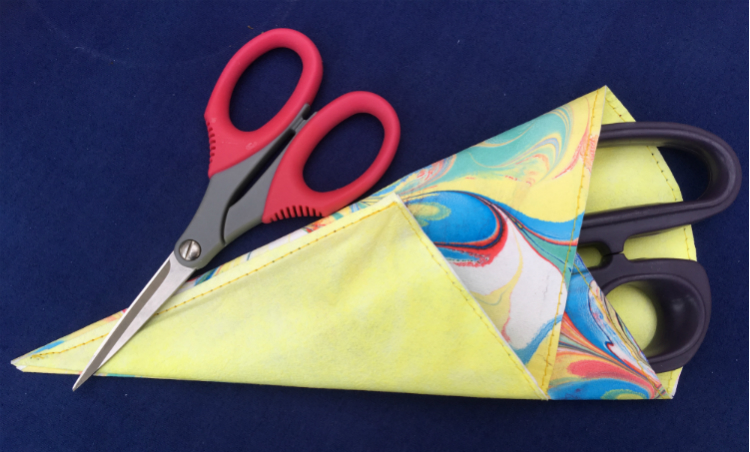 Completed scissor sleeve, containing large purple scissors with small red pair lying across the top.