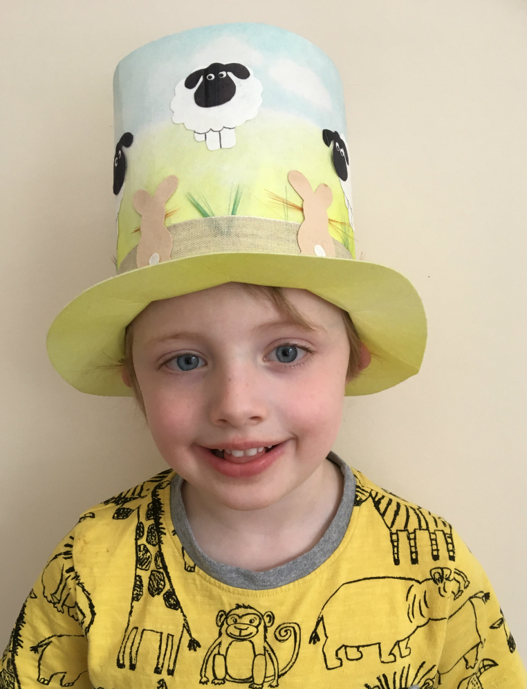 Young boy wearing Easter top hat, decorated with sheep and rabbits.
