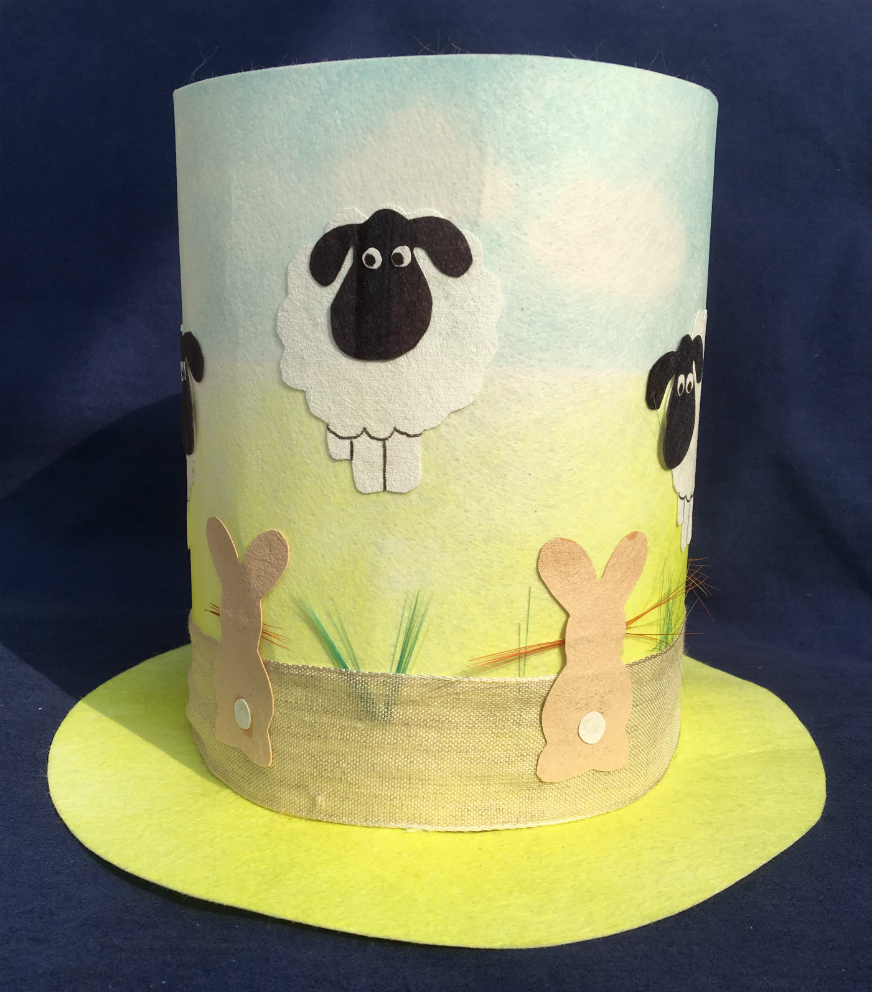 Child's Easter bonnet decorated with white sheep with black faces and light brown rabbits.