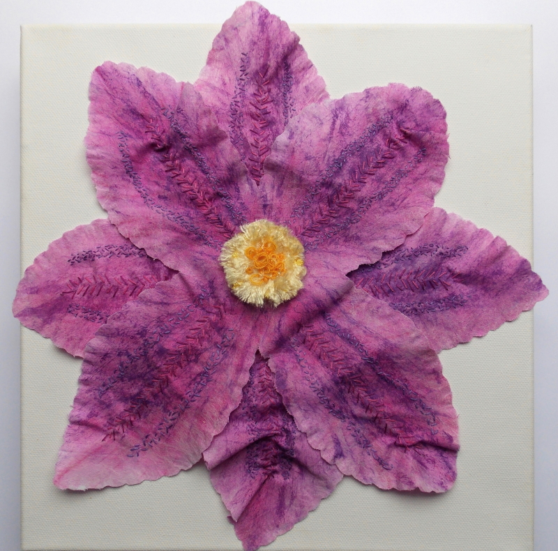 Single crimson/mauve flower with eight petals decorated with darker stitching and a yellow and orange centre.