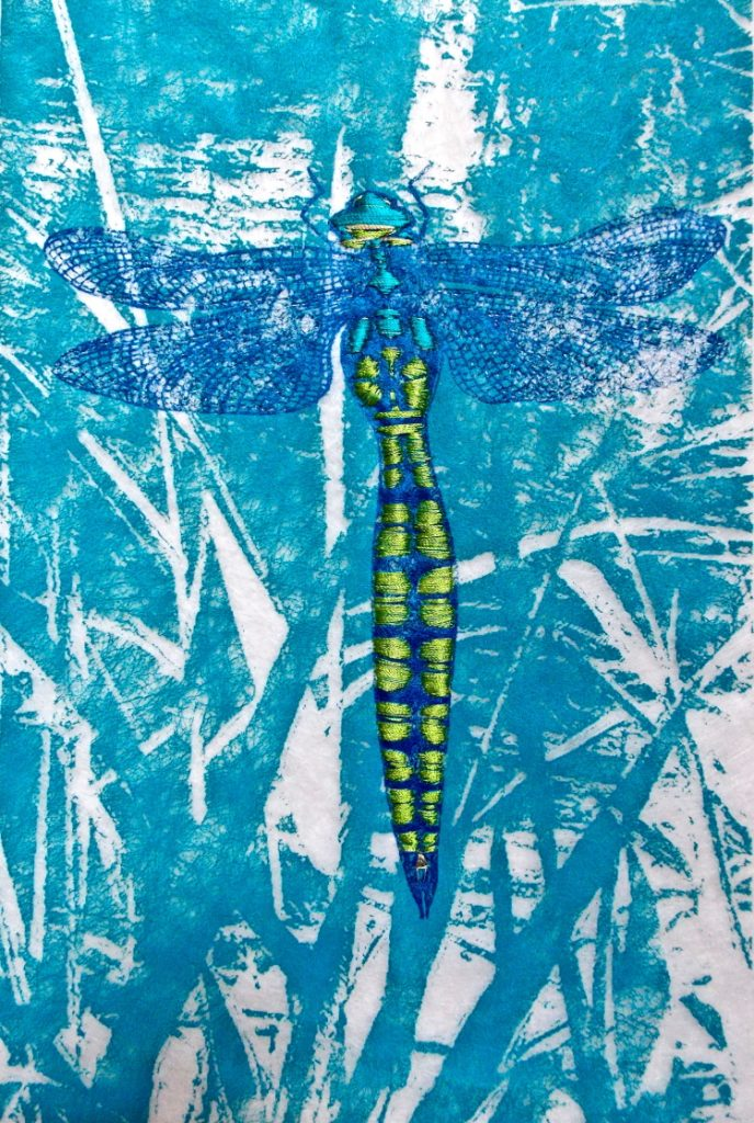 Royal blue dragonfly with lime green embroidery on its body and delicate blue wings against a mid blue and white abstract background.