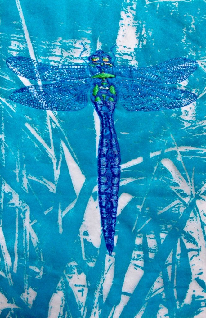Royal blue dragonfly with a small amount of lime green embroidery on its body and delicate blue wings against a mid blue and white abstract background.