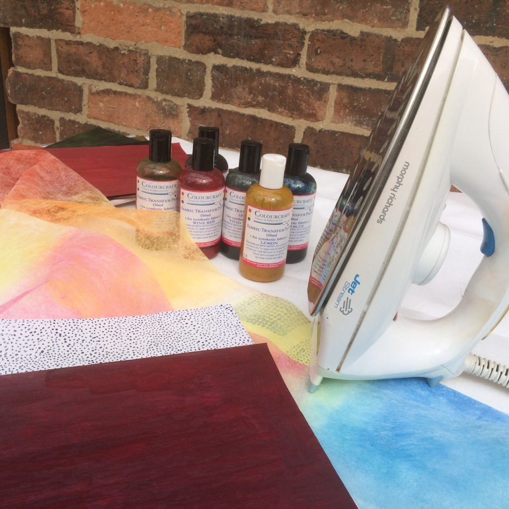 An iron, bottles of transfer paints and sheets of paper which have been painted with transfer paints.