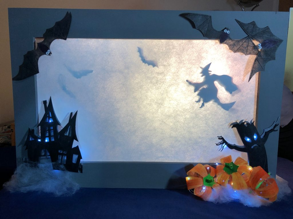The shadow of a witch on a broomstick behind a wide white screen, with a haunted house and spooky tree in front of the screen. The house and the tree are both painted black, but lit with battery operated lights. Three orange pumpkins rest at the base of the tree and three big bats decorate the top of the screen.