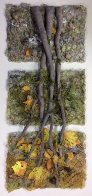 Three separate landscape sections, representing the earth, joined together by three long grey roots. The background sections are made up of little stones, moss and leaves in autumnal shades of grey, green, yellow and orange.