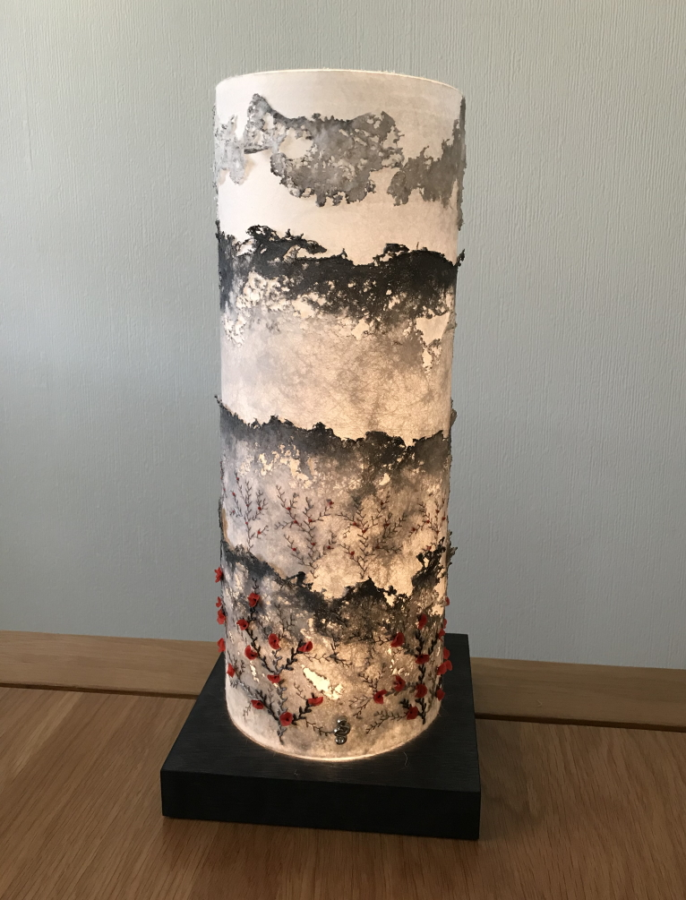 A tall cylindrical lampshade, made up of four layers of Lutradur in decreasing height. Each layer is tinged with grey and has been distressed with a heat gun to give a rough edge.