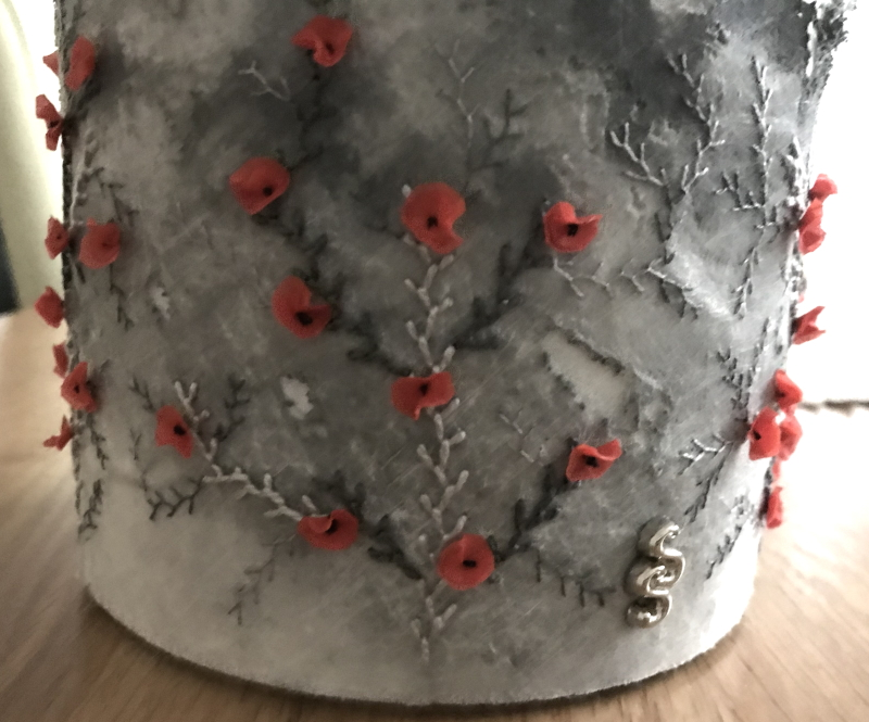 Close up photograph of the base section of the lampshade showing the embroidery and small silk poppies, which Sylvia has used to embellish the surface of the lampshade.
